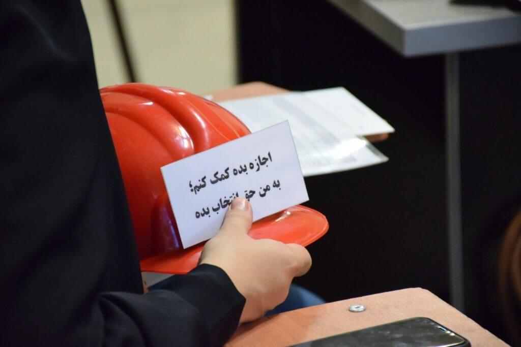 کلاهی در دست مادر شرکت کننده در کارگاه است که روی آن نوشته: «اجازه بده کمک کنم، به من حق انتخاب بده».