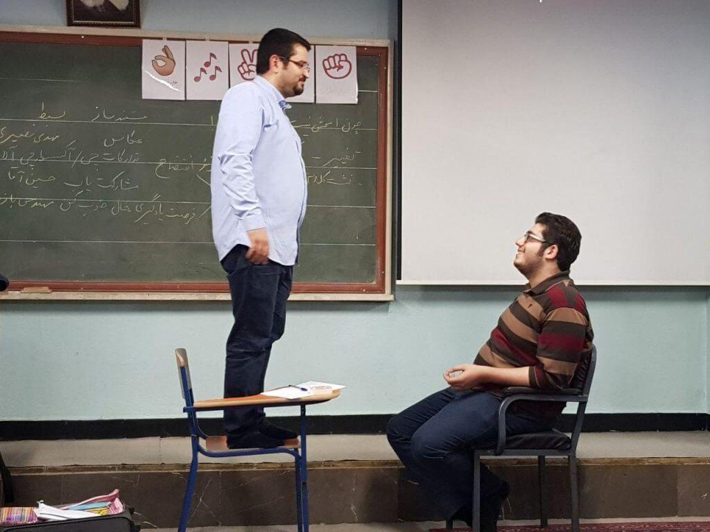 یکی از مدرسان تربیت سالم روی صندلی ایستاده و یکی از والدین در مقابلش روی صندلی نشسته است